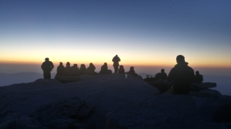 A group of dedicated hikers sit still on the summit of the tallest mountain in the continental United States waiting for the sun to rise.