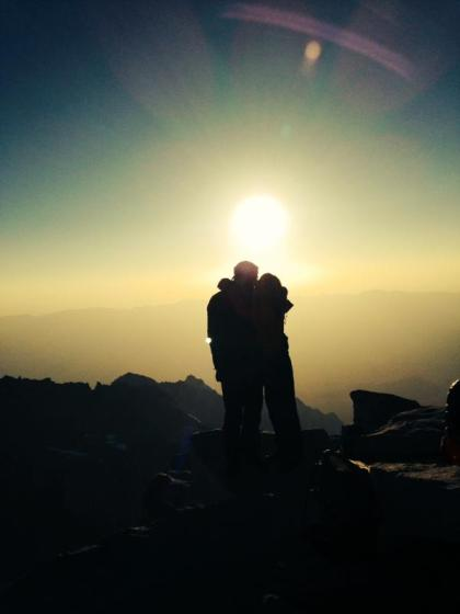 On the highest point with my love. Kissing as the sun rises.