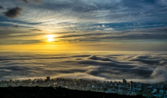 Looking out from Signal Hill in Cape Town, South Africa. With enough pressure the normal atmospheric properties invert, causing a warm layer of air to cause a 'cap' in the air trapping the cooler air underneath it. In this case, it trapped the fog over the water and made for an incredible sight!
