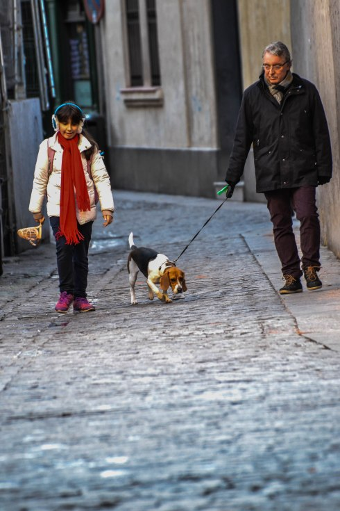 A grandfather and his granddaughter go for an afternoon stroll in the old town of Madrid with their loyal companion.