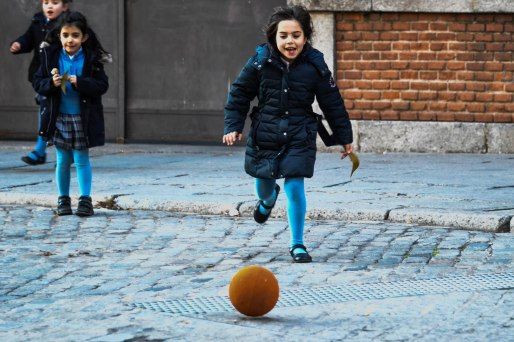 School children playing kickball around an old square in Madrid.