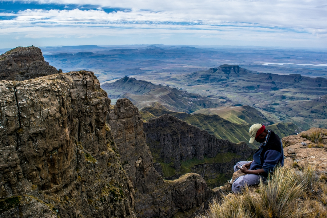 Tendai, a zimbawean porter sits nonchalantly on a 4,000 foot cliff.