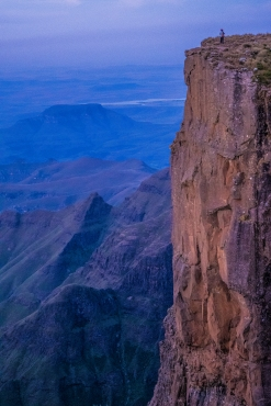 A lone hiker stands on the edge of the Drakensberg during the sunset. The high places are what keep up going in the low.
