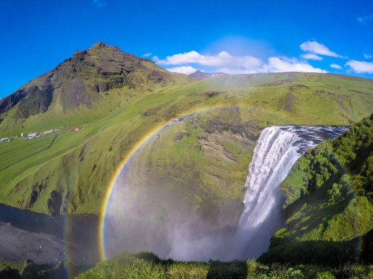 On top of Skogafoss Waterfalls with rainbows.