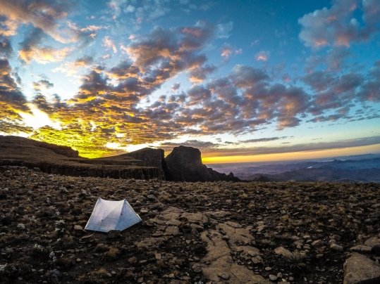Camping on the edge of the High Drakensberg. The cliff edge was about forty feet away from the tent, dropping over 4,000 feet to the valley below. In the background, the sun sets behind the 'Eastern Buttress'. My favorite campsite of all time.
